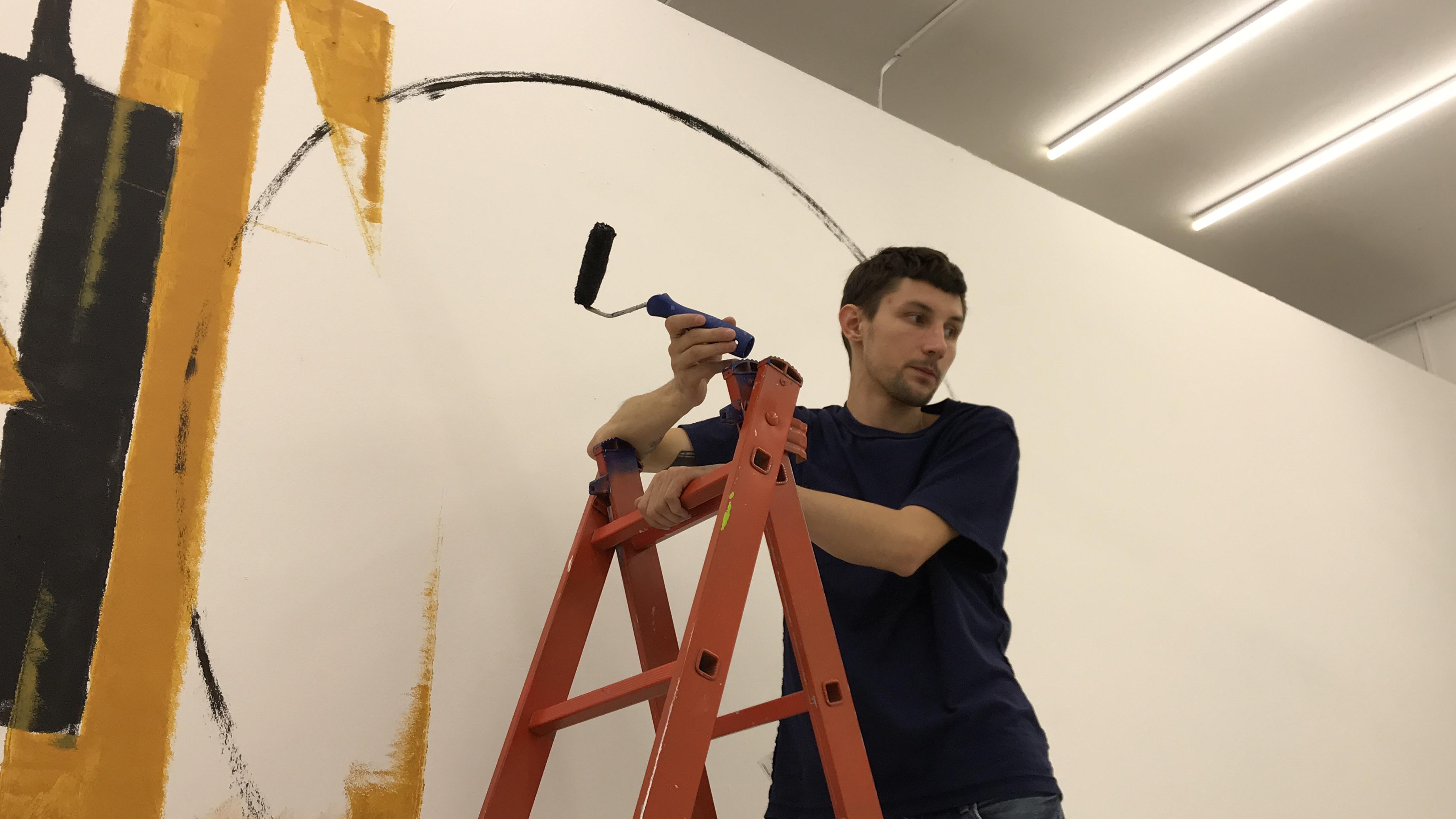Матвей работает над надписью на стене. Фото: Анна-Полина Ильина