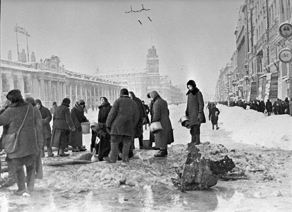 Декабрь 1941 года. Жители Ленинграда набирают воду в пробоинах в асфальте после артобстрела. Фото: Борис Кудояров, РИА Новости