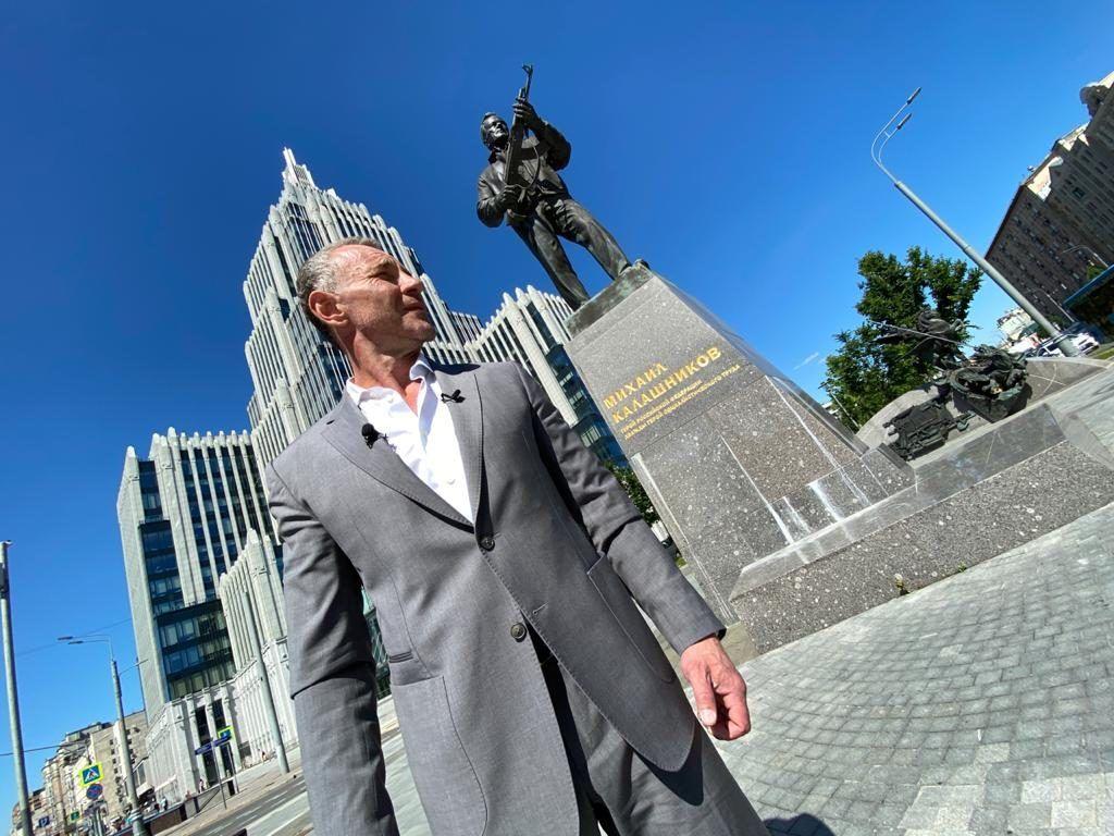 Ведущий Максим Дрозд на фоне памятника Калашникову. Фото предоставили в ГБУ «Центр»