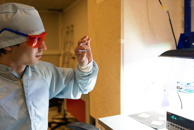 31 августа 2020 года. Инженер университета «МИСиС» Данила Саранин проверяет солнечную батарею (1), которая выполнена в форме небольшого стикера и легко крепится к гаджету (2). Фото: пресс-служба МИСиС